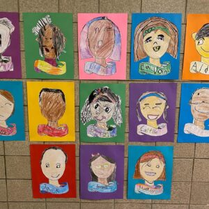 student self-portraits hanging in hall